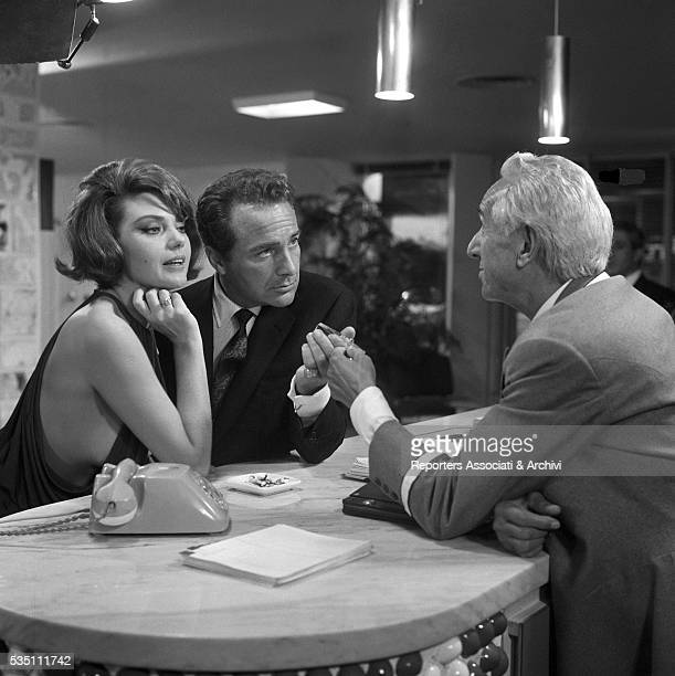 Italian actors Rossano Brazzi and Sylva Koscina getting their room key from the hotel concierge in the segment La lepre e la tartaruga from the film...