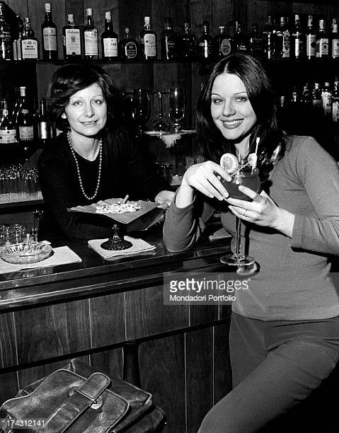 Italian actress Agostina Belli smiling holding a cocktail in the bar of her sister Armida Magnoni Milan 1973