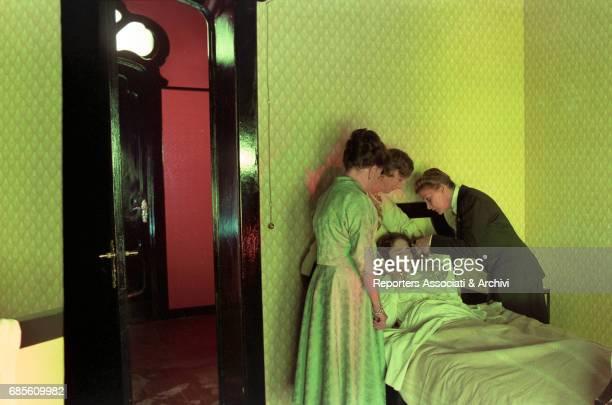 Italian actress Alida Valli giving water to American actress Jessica Harper lying in bed in 'Suspiria' 1977