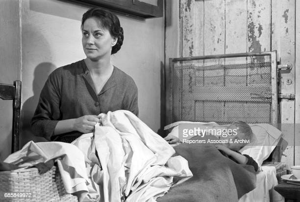 Italian actress Alida Valli sewing a bedsheet in The Wide Blue Road Italy 1957