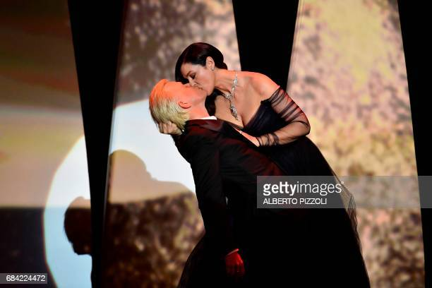 TOPSHOT Italian actress and master of ceremonies Monica Bellucci and French comedian Alex Lutz kiss as they perform on stage on May 17 2017 during of...