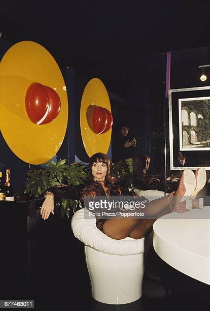 Italian actress and model Elsa Martinelli pictured reclining on a chair part of a range of furniture she personally designed and featuring at a...