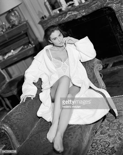 Italian actress and model Monica Bellucci wears a white camisole designed by Chantal Thomass and bathrobe by Hermes