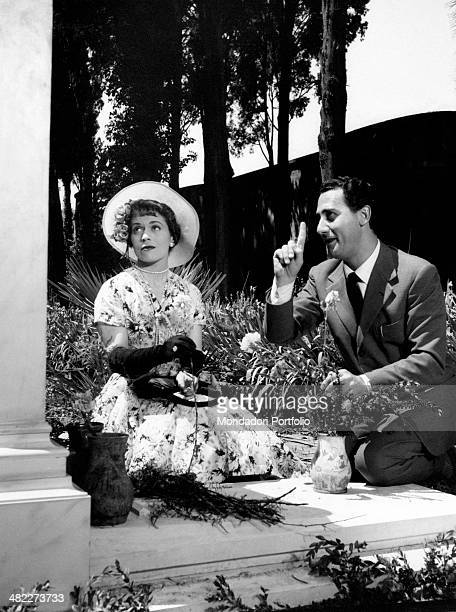 Italian actress and scriptwriter Franca Valeri and Italian actor and director Alberto Sordi pointing and looking up kneeling on a grave in the film A...