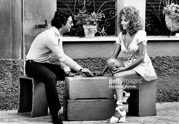 Italian actress and singer Maria Grazia Buccella sitting and talking with her fiancée the film producer Vittorio Cecchi Gori Rome 1970s