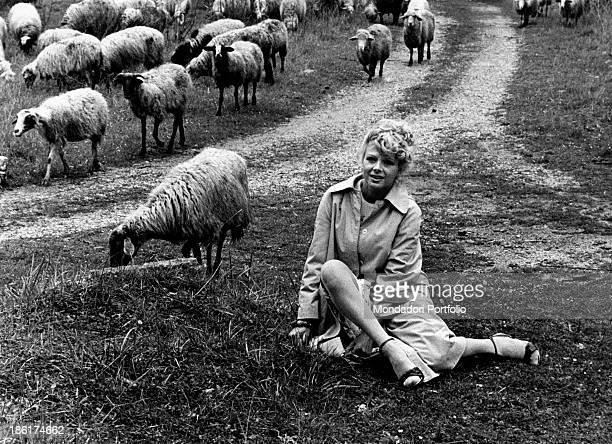 Italian actress and TV presenter Sandra Milo posing in a raincoat beside a flock of sheep 1978