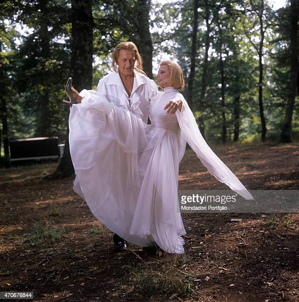 'Italian actress and TV presenter Sandra Mondaini in a white dress lifting her leg helped by her husband and Italian TV host Raimondo Vianello...