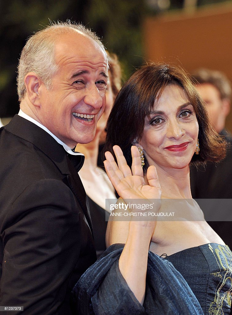 Italian actress Anna Bonaiuto waves as she poses with fellow actor Toni Servillo upon arriving to attend the screening of Italian director Paolo...
