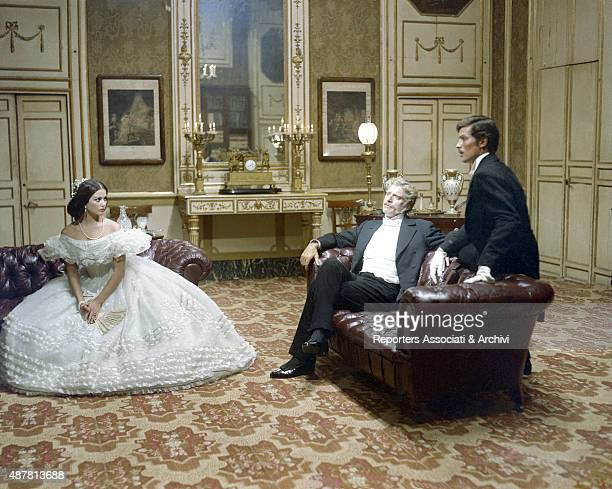 Italian actress Claudia Cardinale in a large ball gown French actor Alain Delon and American actor Burt Lancaster talking in living room in The...