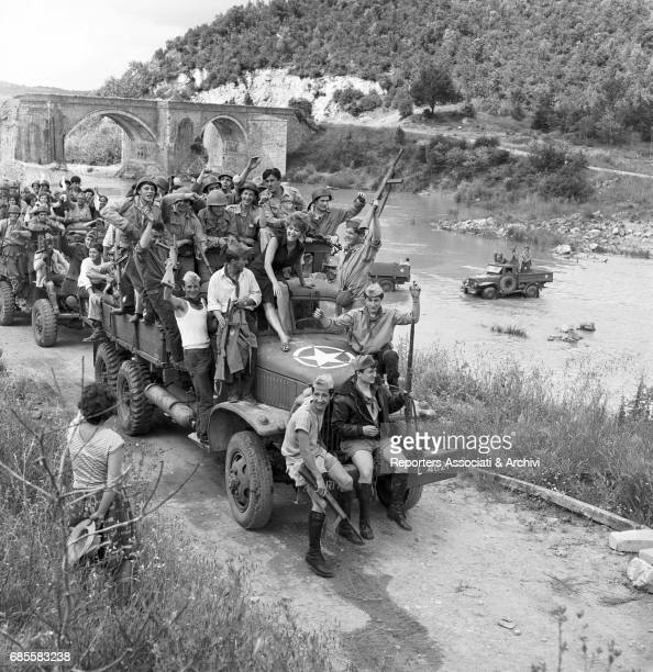 Italian actress Claudia Cardinale sitting on the roof of the truck cab together with many partisans Scene from the film 'Bebo's Girl' directed by...