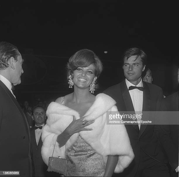 Italian actress Claudia Cardinale wearing a fur and prescious earrings portrayed during an evening party with Jean Sorel Lido Venice 1965