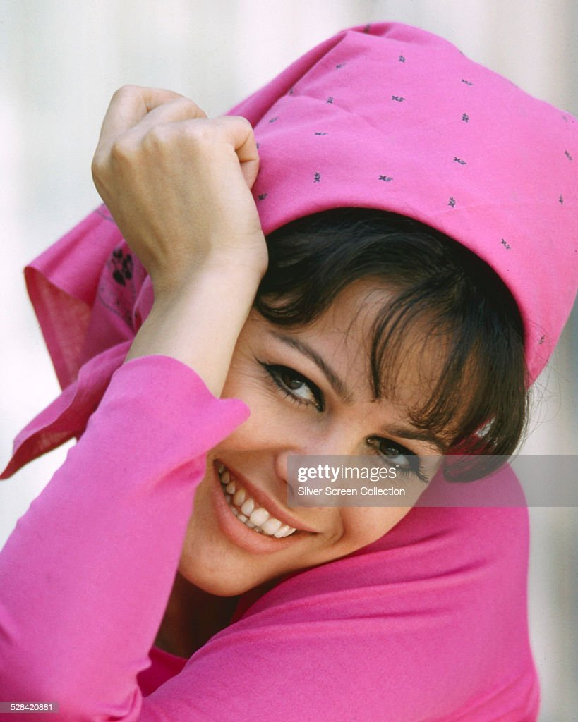 Italian actress <a gi-track='captionPersonalityLinkClicked' href=/galleries/search?phrase=Claudia+Cardinale&family=editorial&specificpeople=208838 ng-click='$event.stopPropagation()'>Claudia Cardinale</a> wearing a pink top and headscarf, circa 1965.