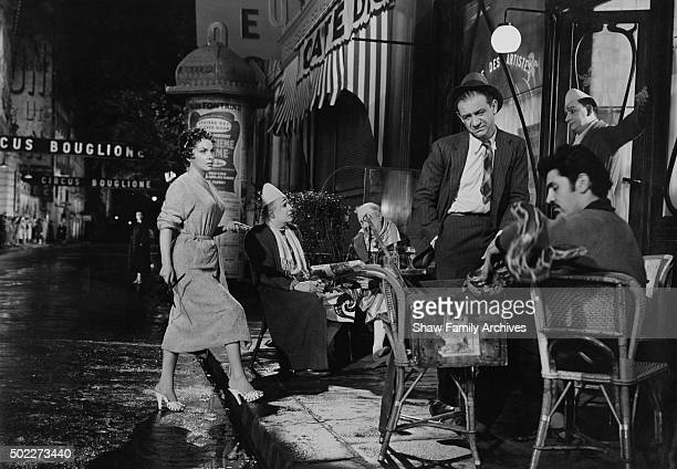 Italian actress Gina Lollabrigida approaches Sid James at an outdoor cafe busy with performers and clowns in 1955 during the filming of 'Trapeze' in...