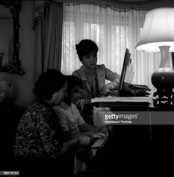 Italian actress Gina Lollobrigida looking at her son Andrea Milko Skofic learning to play the piano Her son was born in 1957 from the marriage with...