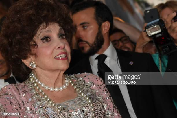 Italian actress Gina Lollobrigida looks on as she poses for photographers in Via Condotti to celebrates her 90th birthday on the red carpet in front...