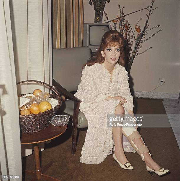 Italian actress Gina Lollobrigida pictured sitting in a chair with a splint and bandages on her leg in a hospital in Rome Italy as she recovers from...