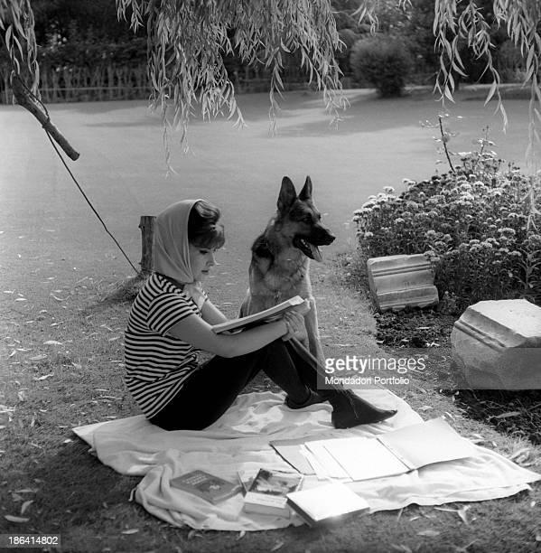 Italian actress Gina Lollobrigida reading a script sitting on a cloth beside a German Shepherd 1960s