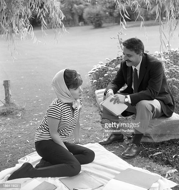 Italian actress Gina Lollobrigida sitting on a cloth interviewed by Italian journalist Giorgio Torelli 1960s