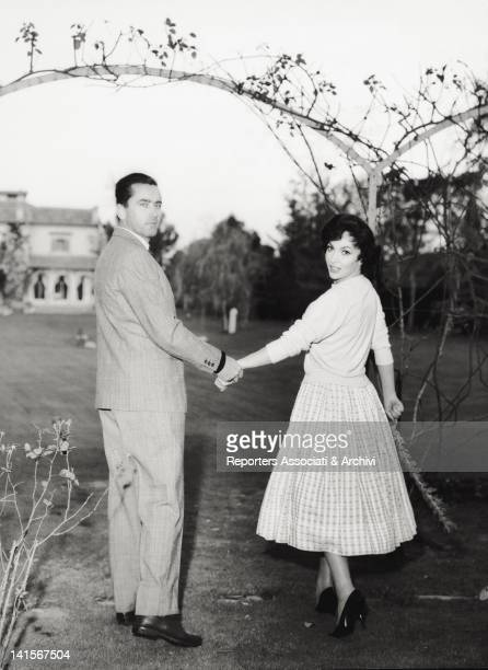 Italian actress Gina Lollobrigida walking hand in hand with her husband Slovenian doctor Milko Skofic in the garden of their residence on the Appian...