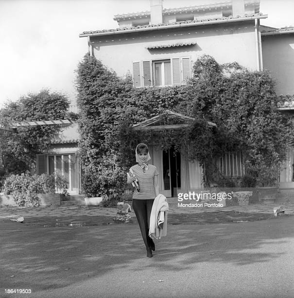 Italian actress Gina Lollobrigida walking with a cloth and some books under her arm 1960s