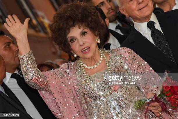 Italian actress Gina Lollobrigida waves as she poses for photographers in Via Condotti to celebrates her 90th birthday on the red carpet in front of...