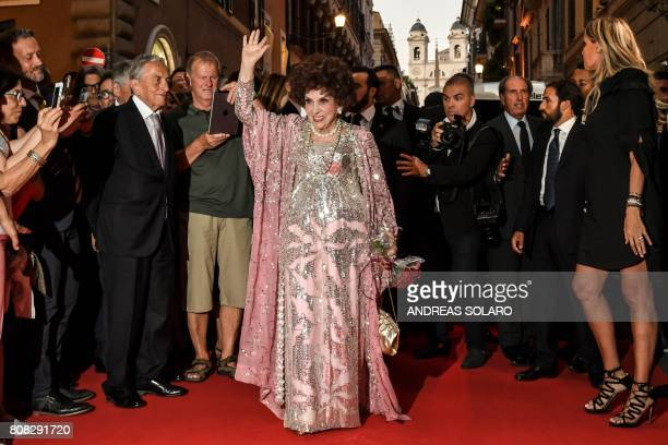 TOPSHOT Italian actress Gina Lollobrigida waves as she poses for photographers in Via Condotti to celebrates her 90th birthday on the red carpet in...
