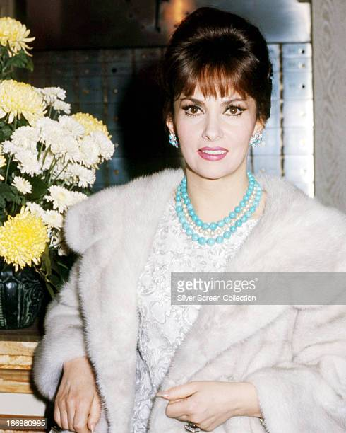 Italian actress Gina Lollobrigida wearing a white fur coat and a blue necklace circa 1963