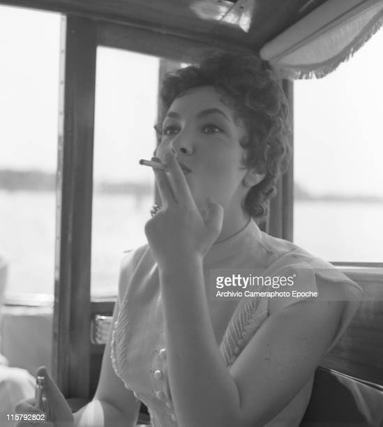 Italian actress Gina Lollobrigida wearing an embroidered dress smoking a cigarette and holding a lighter Venice 1954