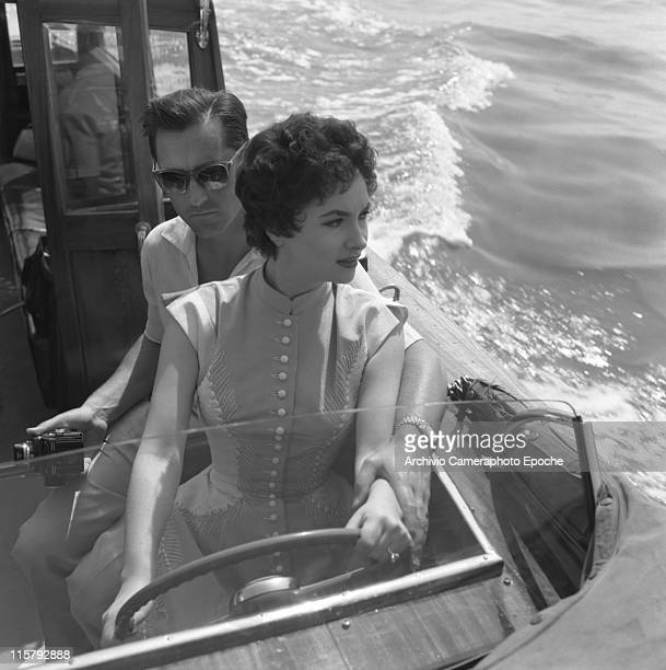 Italian actress Gina Lollobrigida wearing an embroidered dress and driving a water taxi helped by her husband Mirko Scofic wearing sunglasses and...