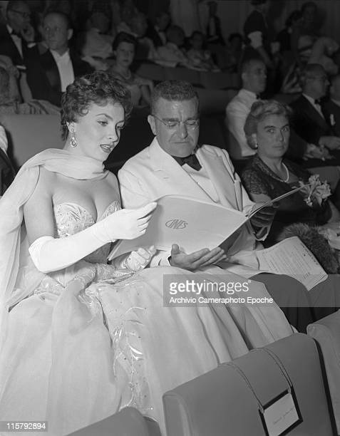 Italian actress Gina Lollobrigida wearing an embroidered evening dress a foulard and gloves sitting in the audience and reading a programme with the...