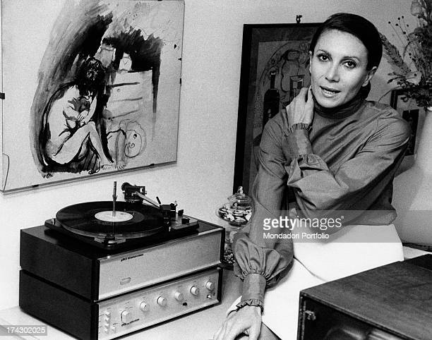 Italian actress Ileana Ghione posing beside a record player Behind her a painting with a female nude Milan 1970s