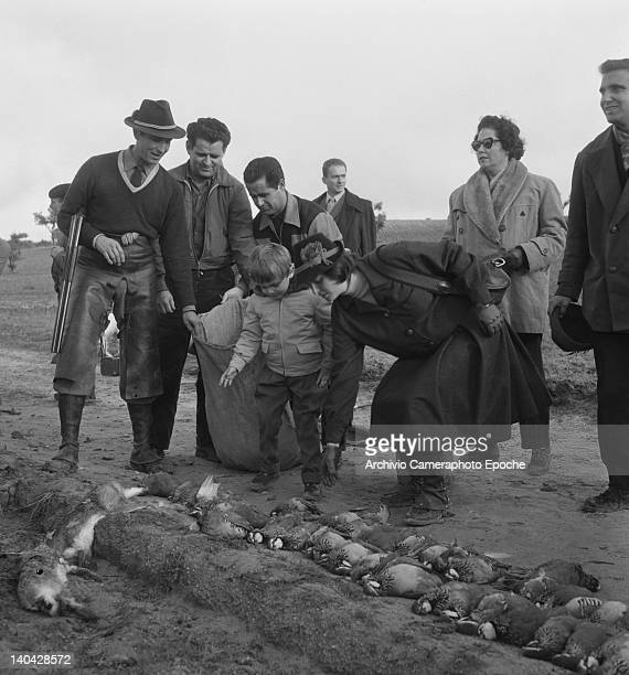 Italian actress Lucia Bose and her son Miguel Bose checking the the partridges on the floor Madrid 1961