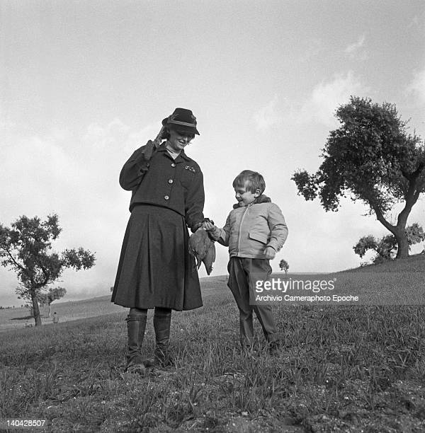 Italian actress Lucia Bose and her son Miguel Bose holding a dead partridge Madrid 1961