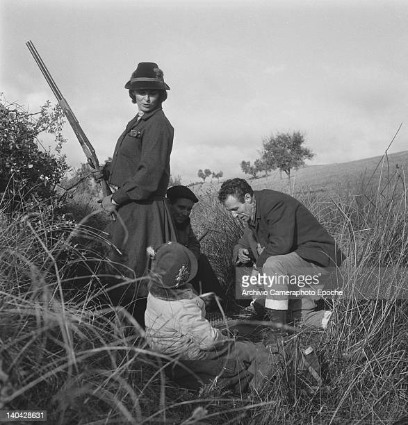 Italian actress Lucia Bose and her son Miguel Bose portrayed while hiding behind a bush during a hunting trip Madrid 1961