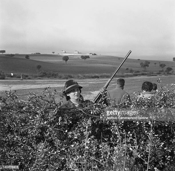 Italian actress Lucia Bose hiding behind a bush during a hunting trip Madrid 1961