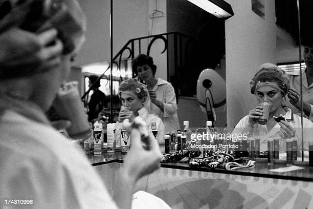 Italian actress Lydia Alfonsi drinking something at the hair stylist 1960