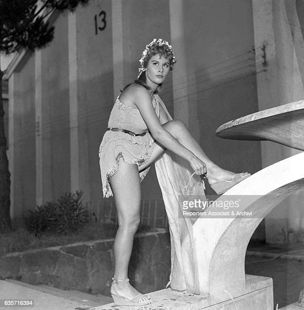 Italian actress Marisa Allasio wearing eer stage costume lacing up her sandal in the streets of Cinecittò during a break from the shooting of the...