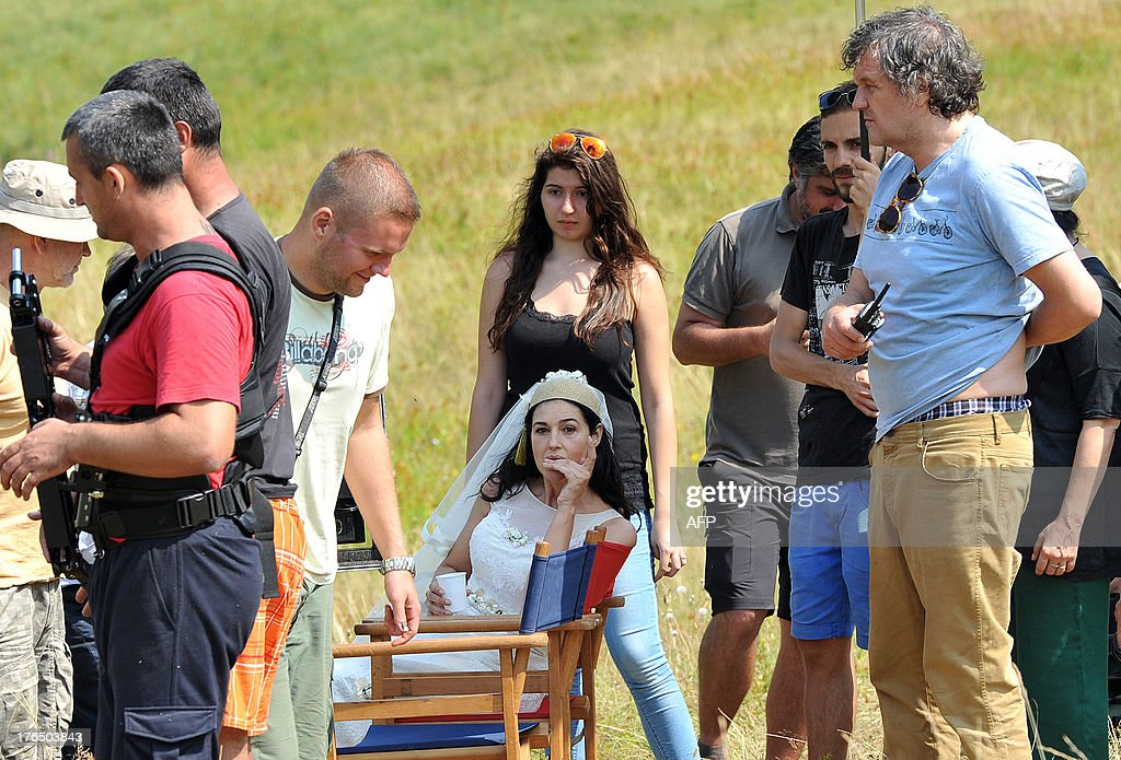 Italian actress Monica Bellucci (C) is seen on the set of the new movie by internationally acclaimed Serbian director Emir Kusturica (R) near the town of Gacko, southeastern Bosnia on August 14, 2013. Bellucci has started filming for the new movie 'The Milky Road', expected to be presented in Cannes in 2014. AFP PHOTO / MILOS CVETKOVIC OUT--
