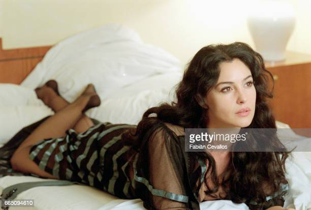 Italian actress Monica Bellucci wearing a black dress lies on a bed on the set of the Italian director Giuseppe Tornatore's film Malena On the day...