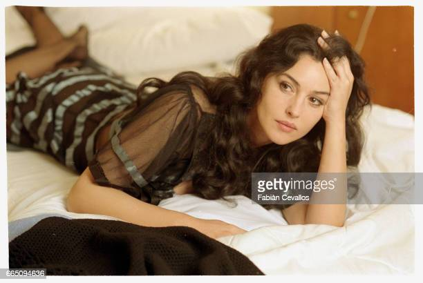 Italian actress Monica Bellucci wearing a black dress lies on a bed with her hand on her head on the set of the Italian director Giuseppe Tornatore's...