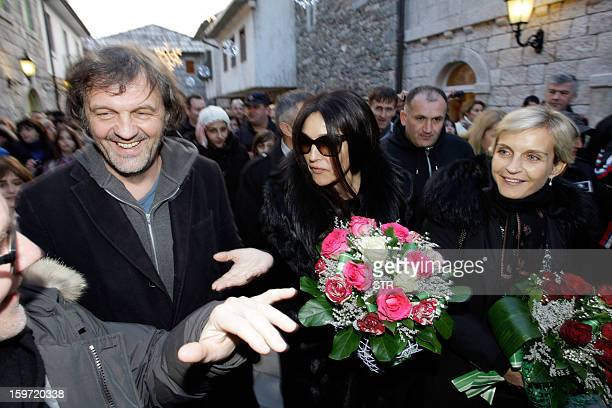 Italian actress Monica Belluci speaks with a person alongside Bosnianborn film director Emir Kusturica as they walk through the center of the eastern...