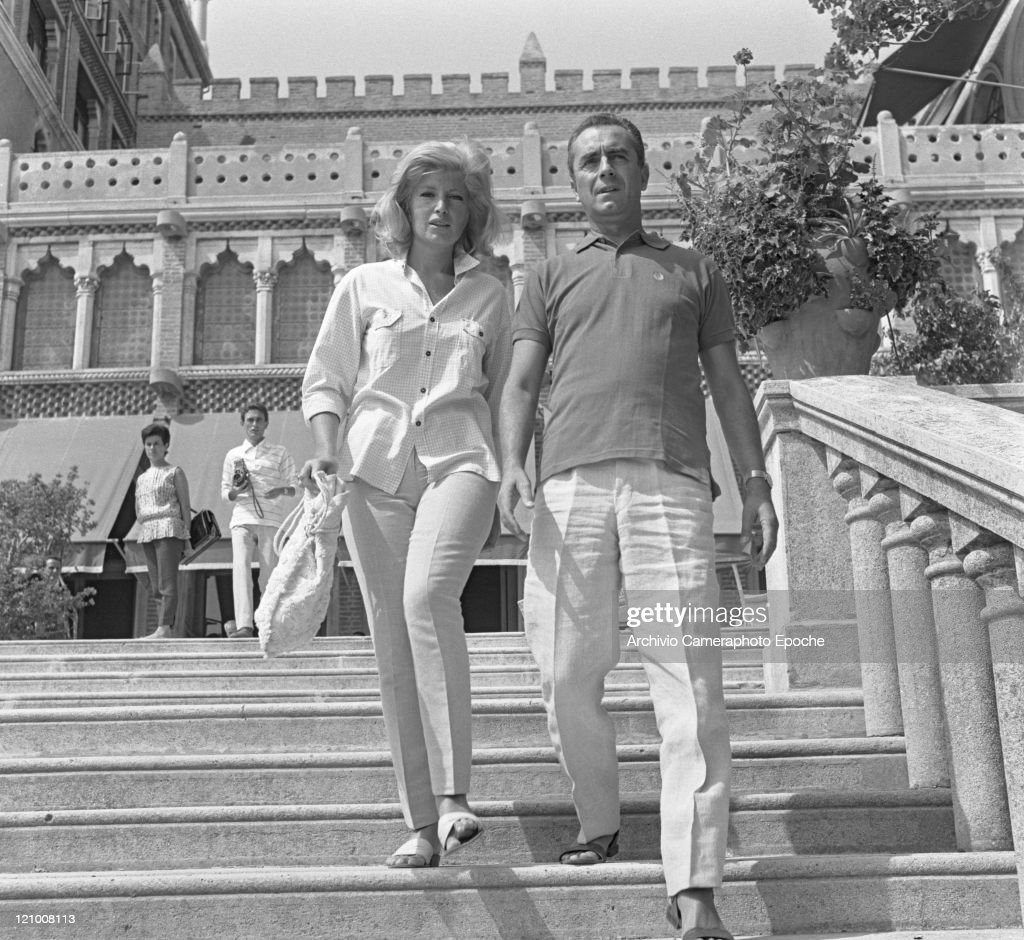 Italian actress Monica Vitti holding a handbag and italian actor Michelangelo Antonioni portrayed while descending the Excelsior Hotel stairs Lido...