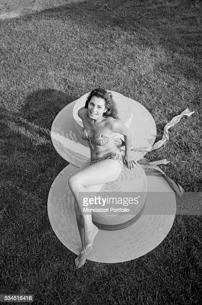 Italian actress Rosanna Schiaffino in a bikini lying on giant hats during the XVIII Venice International Film Festival Venice 1957