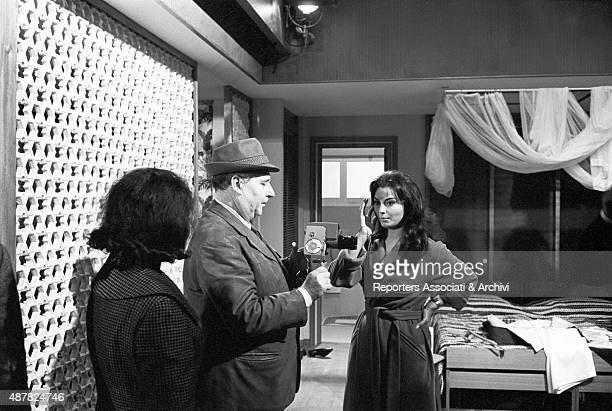 Italian actress Rosanna Schiaffino looking at Italian director Roberto Rossellini holding a camera on the set of the film Rogopag segment Chastity...