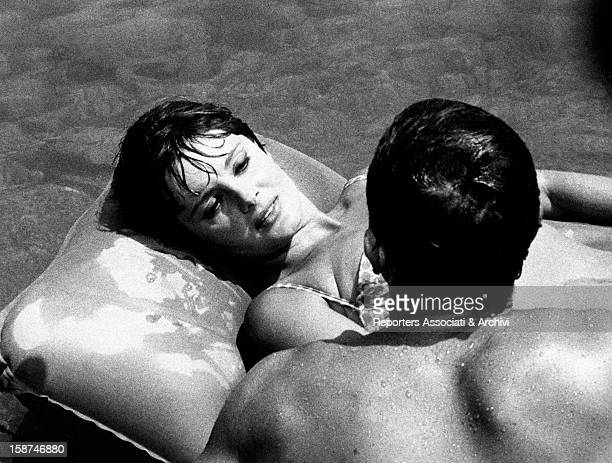 Italian actress Rossana Podestà lying on an inflatable mattress and looking at a man in The Naked Hours 1964