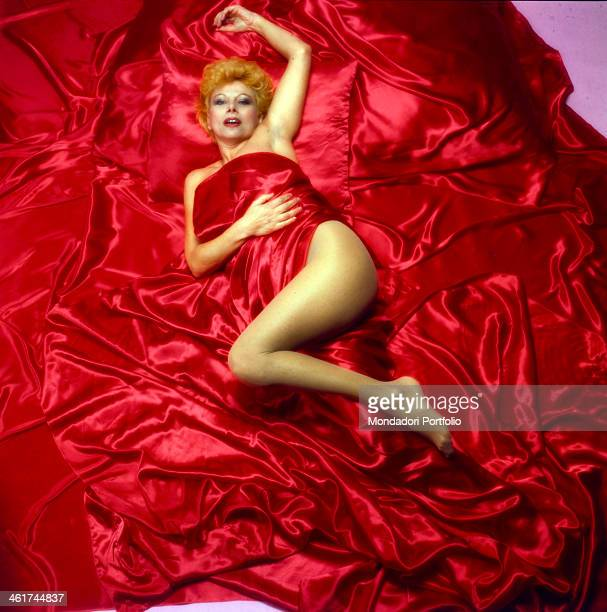 Italian actress Sandra Milo posing wrapped in a red sheet 1983