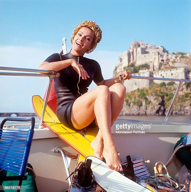 Italian actress Silvana Pampanini is shot during a moment of relax while she is spontaneously smiling and sitting crosslegged on the edge of a boat...