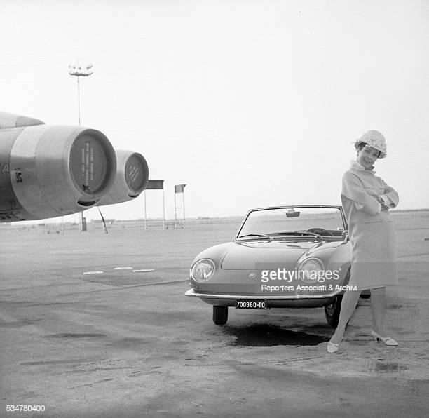 Italian actress Silvana Pampanini posing with a Fiat 850 Spider Italy 1965
