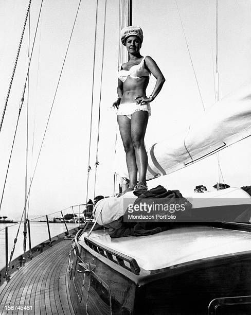 Italian actress Silvana Pampanini wearing a swimsuit and smiling on board a sailboat 1960s