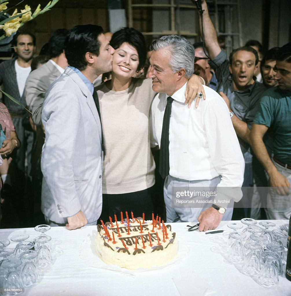 Italian actress Sophia Loren (Sofia Villani Scicolone) celebrating her birthday with Italian director Vittorio De Sica and Italian actor Marcello Mastroianni on the set of the film Yesterday, Today and Tomorrow. 1963